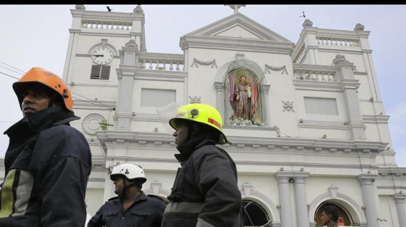 Sri Lankan firefighters stand in the area around St. Anthony's Shrine after a blast in Colombo, Sri Lanka. (Photo: AP)