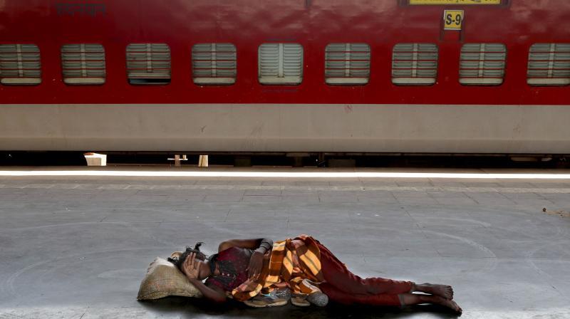A homeless woman sleeps on a deserted platform of the Lokmanya Tilak train terminus in Mumbai. (File photo: AP)