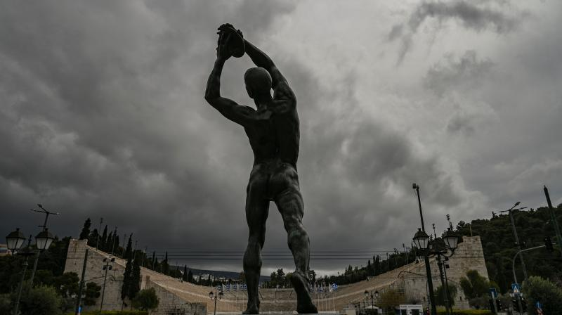 A statue of a discus thrower stands opposite Athens' Panathenaic stadium or Kalimarmaro, where the first modern Olympic Games began, in Athens, one day after the historic decision to postpone the 2020 Tokyo Olympic Games. Japan on March 25 started the unprecedented task of reorganising the Tokyo Olympics after the historic decision to postpone the world's biggest sporting event due to the COVID-19 coronavirus pandemic that has locked down one third of the planet. (AFP)