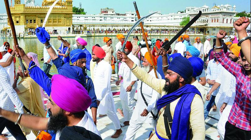Members of various radical Sikh organisations shout pro-Khalistan slogans and brandish swords at a demonstration marking the 35th anniversary of the Operation Blue Star, 1984, at Golden Temple in Amritsar on Thursday. (Photo: PTI)