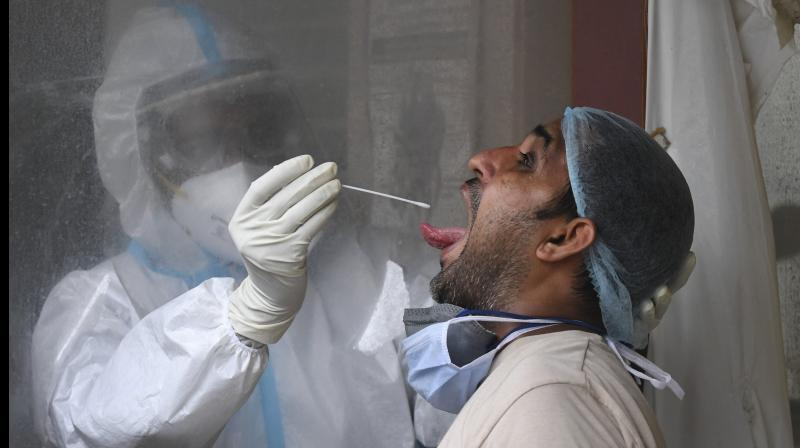 Medic collects samples of people for COVID-19 testing in Delhi. PTI photo