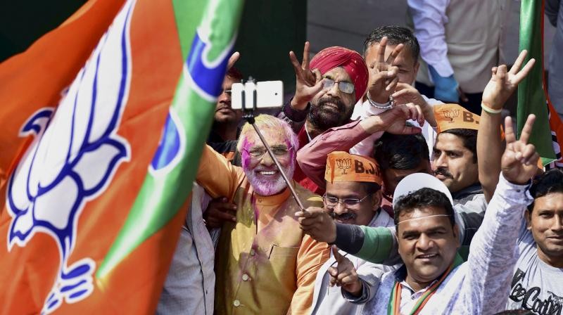A Prime Minister Narendra Modi look-alike flashes victory sign along with other BJP workers as they celebrate the party's victory in the assembly elections, at party headquarters in New Delhi on Saturday. (Photo: PTI)