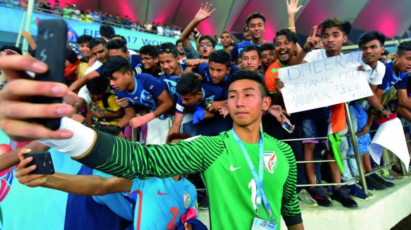 India goalkeeper Dheeraj Moirangthem takes a selfie with his fans after their last group match against Ghana in New Delhi on Thursday. (Photo: PTI )