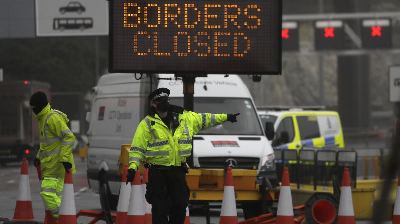 A police officer directs traffic at the entrance to the closed ferry terminal in Dover, England, Monday, Dec. 21, 2020, after the Port of Dover was closed and access to the Eurotunnel terminal suspended following the French government's announcement. (AP)