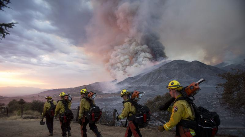 Members of firefighters walk in line during a wildfire in Yucaipa, Calif., Saturday, Sept. 5, 2020. Three fast-spreading California wildfires sent people fleeing Saturday, with one trapping campers at a reservoir in the Sierra National Forest, as a brutal heat wave pushed temperatures into triple digits in many parts of state.(AP)