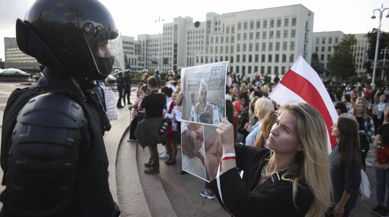 A woman shows a photo of bitten detained protesters to riot police at Independence Square during an opposition rally to protest the official presidential election results in Minsk, Belarus, Saturday, Sept. 5, 2020. Women's marches and demonstrations have become a regular feature of the four weeks of protest that have shaken Belarus following a disputed election that gave Belarusian President Alexander Lukashenko a sixth term in office. (AP)