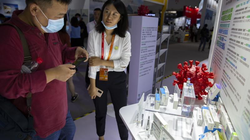 A visitor wearing a face mask looks at a model of a coronavirus and boxes for COVID-19 vaccines at a display by Chinese pharmaceutical firm Sinopharm at the China International Fair for Trade in Services (CIFTIS) in Beijing, Saturday, Sept. 5, 2020. With the COVID-19 pandemic largely under control, China's capital on Saturday kicked off one of the first large-scale public events since the start of the coronavirus outbreak, as tens of thousands of attendees were expected to visit displays from nearly 2,000 Chinese and foreign companies showcasing their products and services. (AP)