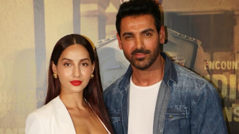 Nora Fatehi with John Abraham. (Photo: Viral Bhayani)