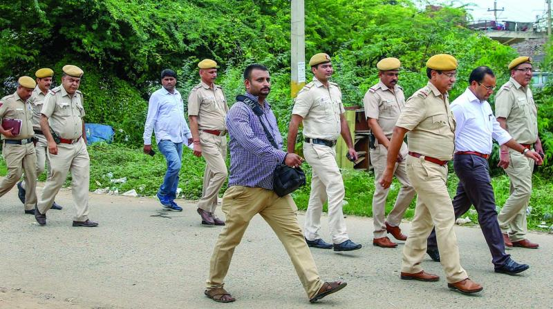 A senior officer, accompanied by a police team, visits the tense area of Rangpuri where a nine-year-old girl was allegedly raped by an unidentified man, on Saturday. (Photo: PTI)