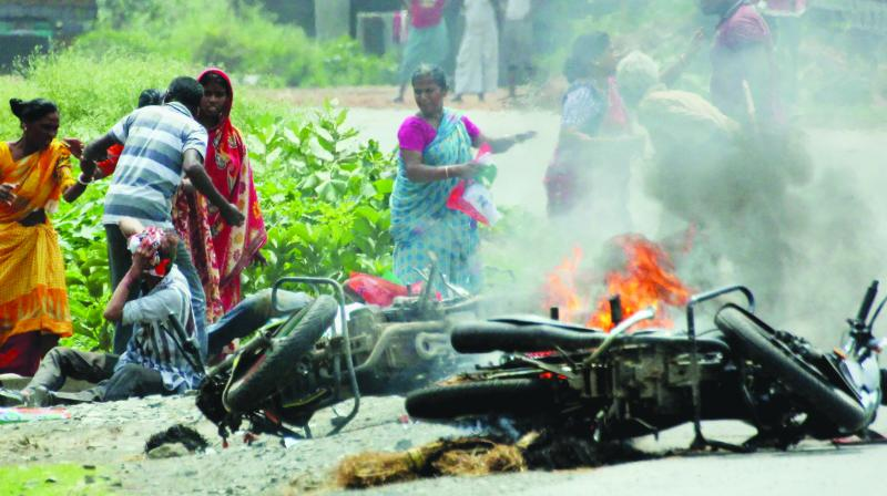 People injured in poll violence sit by the side of a road as a vehicle is set on fire by locals during Panchayat polls, in Nadia district of West Bengal on Monday. (Photo: File/PTI)