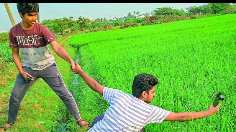 A friend holds Sasi Kumar (sitting) as he leans over the farm field to capture the matting damselfly.