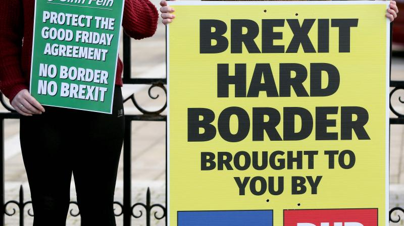 In this file photo taken on October 17, 2018 Students hold up Sinn Fein anti-Brexit placards during a rally against Brexit and any hard border between Ireland and Northern Ireland outside Queens University Belfast, Northern Ireland. (Photo: AFP)