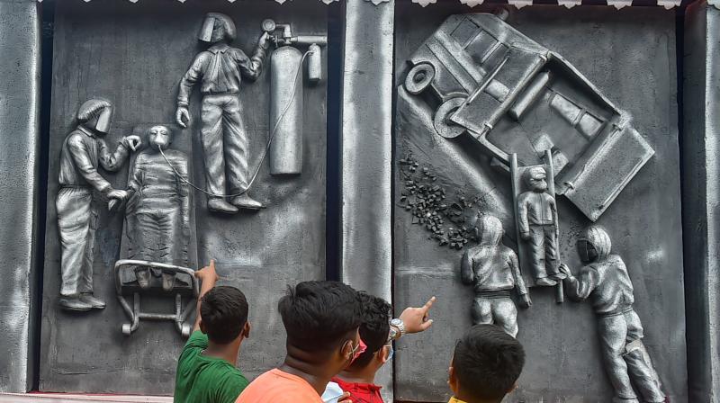 Visitors look at a puja pandal setup on the theme of COVID-19 pandemic, in Kolkata. (Photo: PTI)