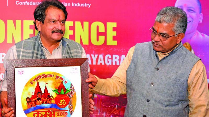 "Uttar Pradesh minister S.P. Singh Baghel and state BJP president Dilip Ghosh release the ""Kumbh 2019"" logo at a press meet in Kolkata on Friday. (Photo: Abhijit Mukherjee)"