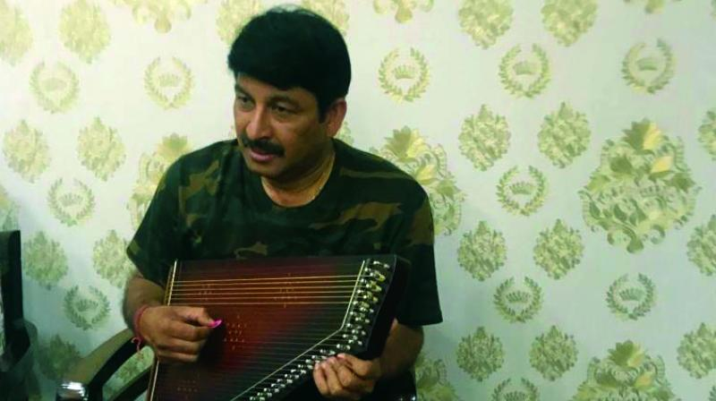 Delhi BJP president and sitting MP Manoj Tiwari plays a musical instrument and Gautam Gambhir with his former teammate Harbhajan Singh in New Delhi on Monday.