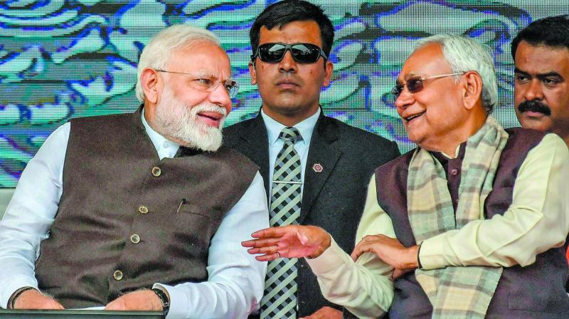 Prime Minister Narendra Modi speaks with Bihar CM Nitish Kumar during the inauguration and foundation stone-laying ceremony of various development projects in Begusarai on Sunday. (Photo: PTI)