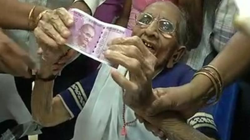 Nonagenarian Heeraben Modi, who had to use the help of a wheel chair and other people to reach the bank, exchanged Rs.4500/- in currency after filling the required forms. (Photo: ANI)