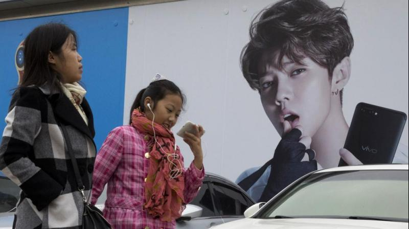 In this Oct. 21, 2017, file photo, Chinese women walk past advertisement featuring teen idol Lu Han, also known as China's Justin Bieber in Beijing. China's government banned effeminate men on TV and told broadcasters Thursday, Sept. 2, 2021 to promote