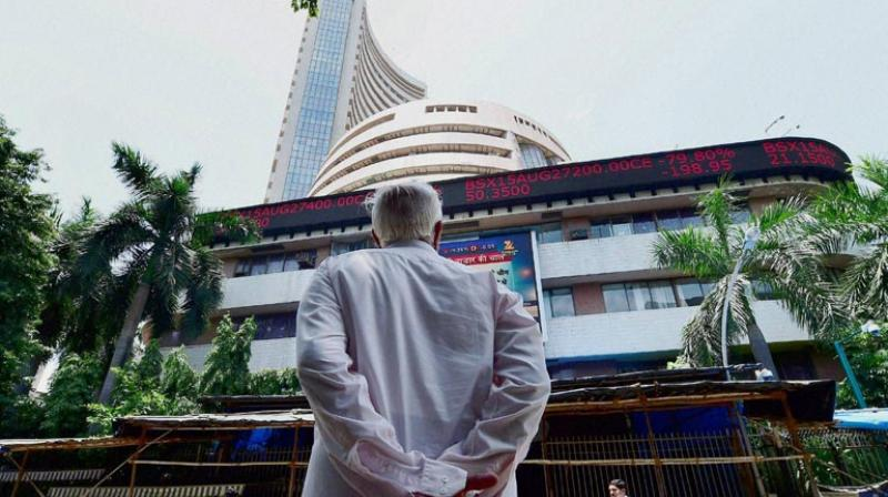 An investors checks changing share prices on an electronic indicator during a session at BSE. (Photo: PTI)