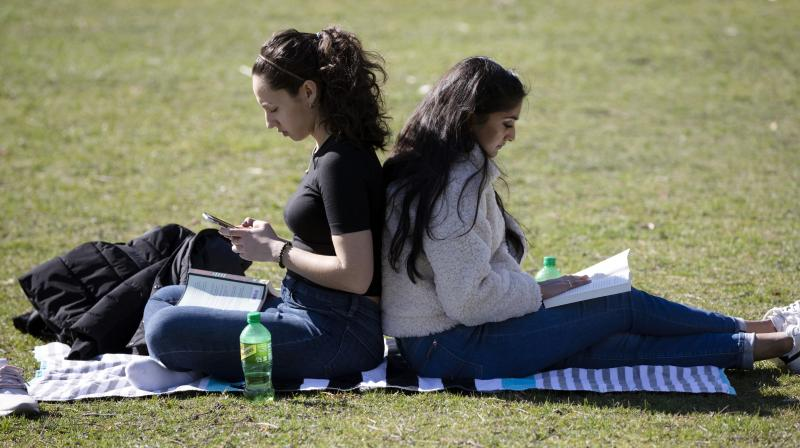 Aesha Patel (right) and her roommate Letitia Klos, both students at Boston University Dental School, read in the Public Garden in Boston on March 27, 2020. The students are currently taking their courses online because all campuses are closed due to the coronavirus. (AP)