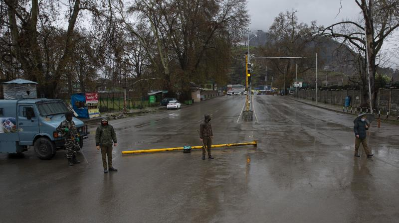 Police and paramilitary soldiers stand guard on a road leading to the Jawaharlal Nehru Memorial Hospital in Srinagar, where most patients with symptoms of COVID-19 are being kept in quarantine. (AP)
