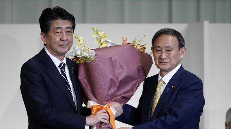 Japan's Prime Minister Shinzo Abe, left, receives flowers from Chief Cabinet Secretary Yoshihide Suga after Suga was elected as new head of Japan's ruling party at the Liberal Democratic Party's (LDP) leadership election, in Tokyo. (AP)
