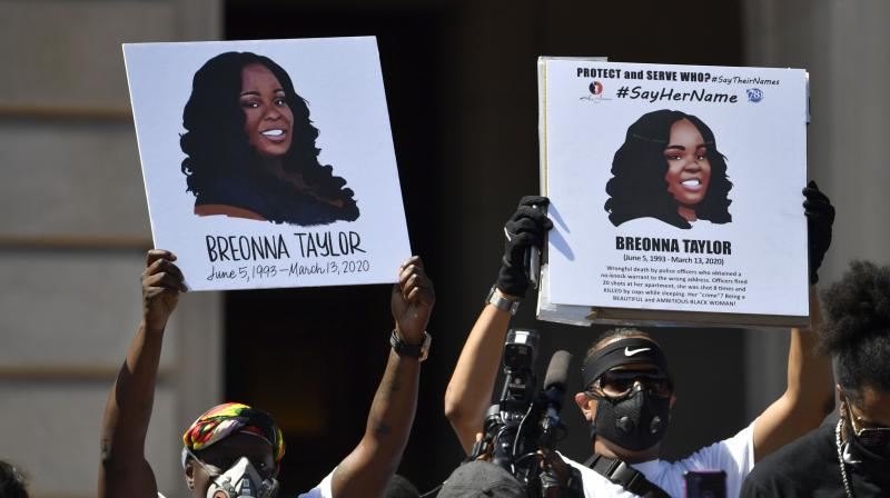 Signs are held up showing Breonna Taylor during a rally in her honor on the steps of the Kentucky State Capitol in Frankfort. The city of Louisville will pay several million dollars to the mother of Breonna Taylor and install police reforms as part of a settlement of a lawsuit from Taylor's family, The Associated Press has learned. (AP)