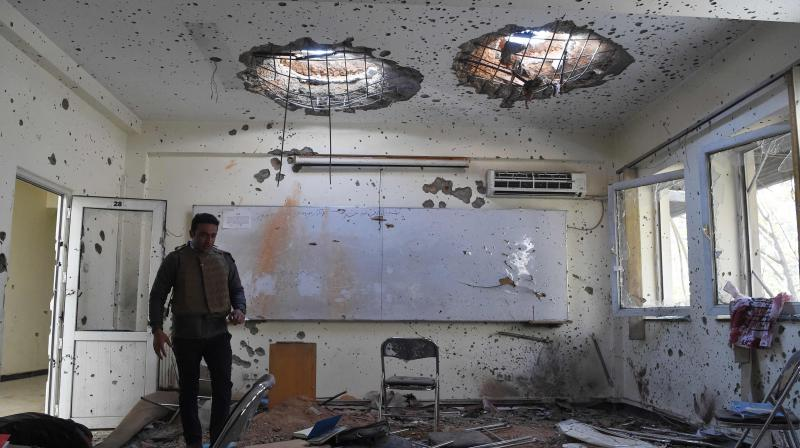 A journalist walks inside of a damaged class of the National Legal Training center, a day after gunmen stormed Kabul university in Kabul on November 3, 2020. - Stunned students demonstrated outside Kabul University on November 3 after at least 22 people were killed in a brutal, on-campus attack claimed by the Islamic State group. (Photo by WAKIL KOHSAR / AFP)