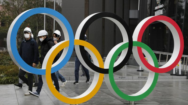 In this March 4, 2020, file photo, people wearing masks walk past the Olympic rings near the New National Stadium in Tokyo. (Photo: AP/File)