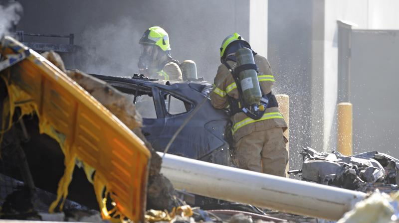 Emergency personnel work at a light plane crashed in Melbourne, Australia, on Tuesday. (Photo: AP)