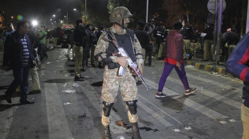 olice and security officers cordon off the area of a deadly bombing, in Lahore. (Photo: AP)