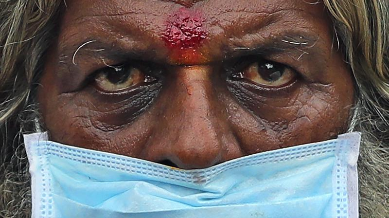 A farmer wearing a face mask listens to a speaker during an anti-government protest in Bengaluru. (AP)