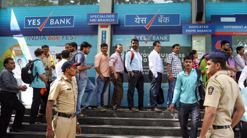 Account holders gather outside Yes Bank to withdraw money, in Thane. PTI photo