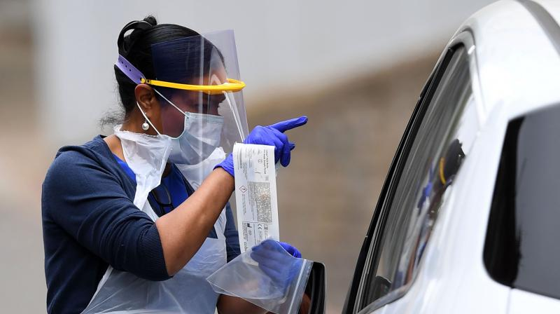 A key worker hands back a swab to a medical worker at a drive-in testing facility for the novel coronavirus COVID-19, in east London. AFP Photo