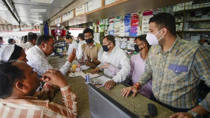 Salesmen at a chemist shop wear protective masks in wake of coronavirus outside Safdarjung Hospital in New Delhi. (Photo- PTI)