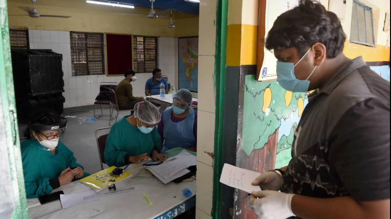 A medic interacts with a man during COVID-19 testing drive via Rapid Antigen at Govt school, in New Delhi. PTI photo