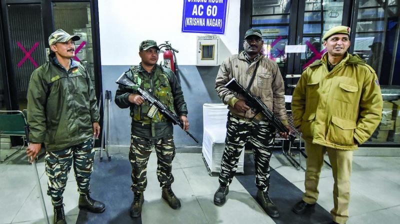 Security personnel stand guard outside a strongroom at a counting centre in Akshardham, New Delhi, on Sunday. (Photo: PTI)