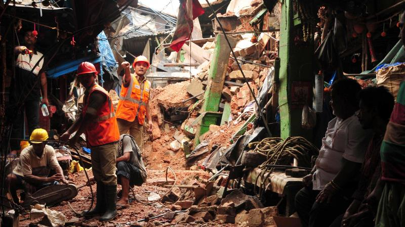 People stand near the debris after a portion of a dilapidated two-storeyed building collapsed in Sealdah area following monsoon rains, in Kolkata on Monday. At least two people died in the accident. (Photo: Abhijit Mukherjee)