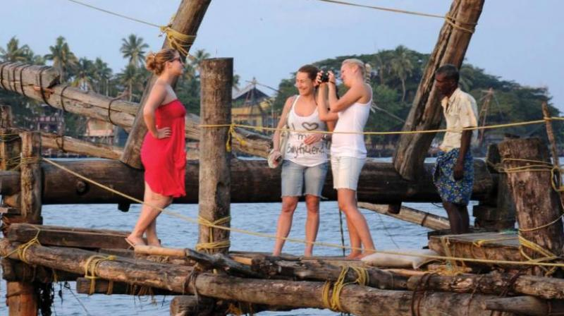Foreign tourists enjoying the famed Chinese fishing nets in Fort Kochi. (DC File Image)
