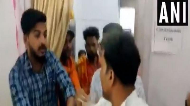 Visuals show the BJP workers raising slogans and slapping the NCP worker, following which he was taken away by the police from the SDM office. (Photo: ANI)