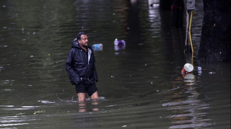 A man stands in a waterlogged street after heavy rainfall in Mumbai. (Photo: AP)
