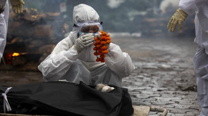 In this file photo, a relative performs last rites before the cremation of a COVID-19 victim in Gauhati. (Photo: AP)