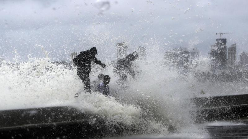 People drench in high tide waves hitting a promenade on the Arabian Sea coast during monsoon rains in Mumbai. (Photo: PTI)