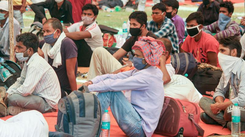 Migrants wait to board a bus for Bihar at Tau Devi Lal Stadium, during the ongoing COVID-19 lockdown, in Gurugram, Tuesday. PTI Photo