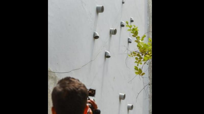 A photographer takes a picture of the 11 pipes protruding out of the house where 11 members of the same allegedly committed suicide, at Burari, in New Delhi. (Photo: PTI)