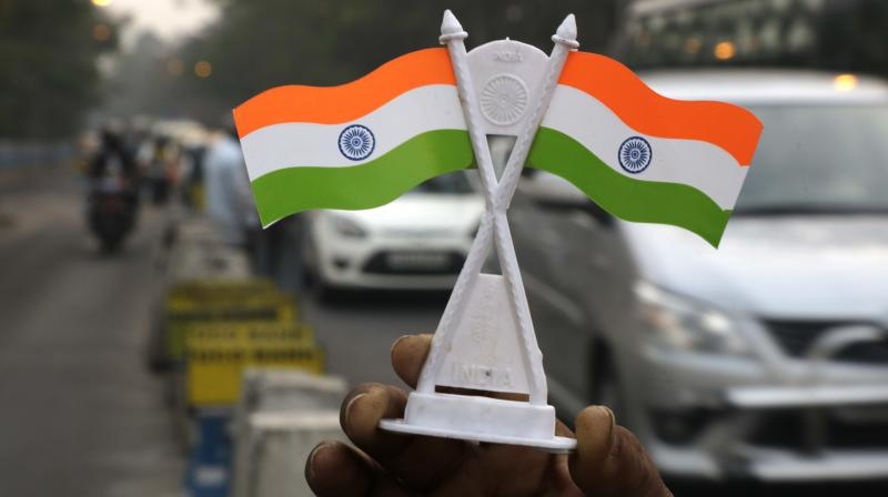 An Indian street vendor sells Indian flags at a traffic intersection on the eve of India's Republic Day, in Kolkata. (Photo: AP)
