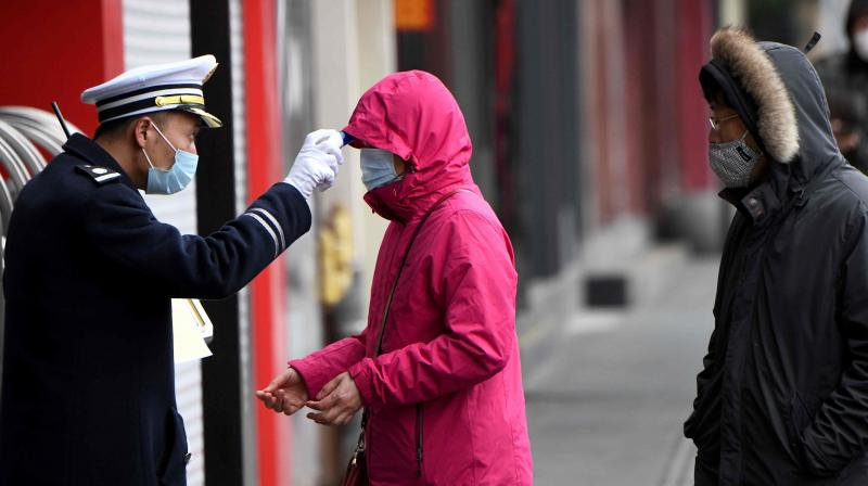 A security guard checks the temperature of people entering Yu Park in Shanghai. AFP photo