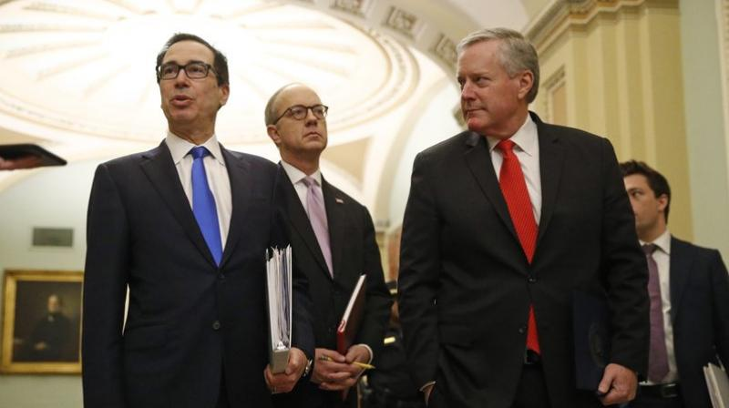 Treasury Secretary Steven Mnuchin, left, accompanied by White House Legislative Affairs Director Eric Ueland and acting White House chief of staff Mark Meadows, speaks with reporters as he walks to the offices of Senate Majority Leader Mitch McConnell of Ky. on Capitol Hill in Washington. (Photo- AP)
