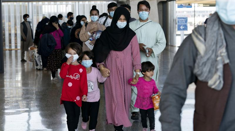 Families evacuated from Kabul, Afghanistan, walk through the terminal before boarding a bus after they arrived at Washington Dulles International Airport, in Chantilly, Va., on Wednesday, Aug. 25, 2021. (AP Photo)