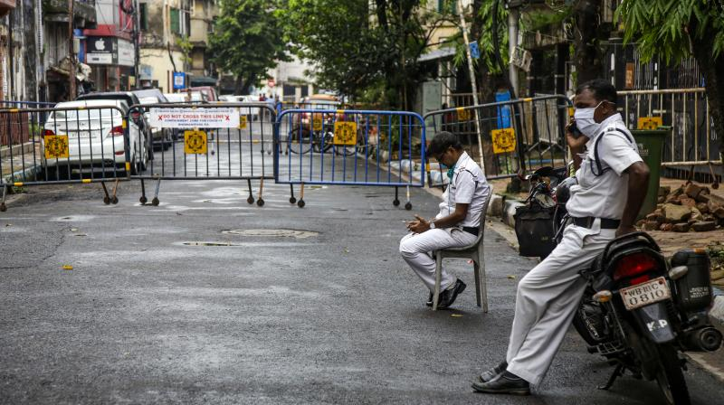 Policemen wearing face masks keep vigil at barricades of a coronavirus containment zone in Kolkata. The Union government has extended the ban on flights to the city in view of the growth in infectionsn. AP)
